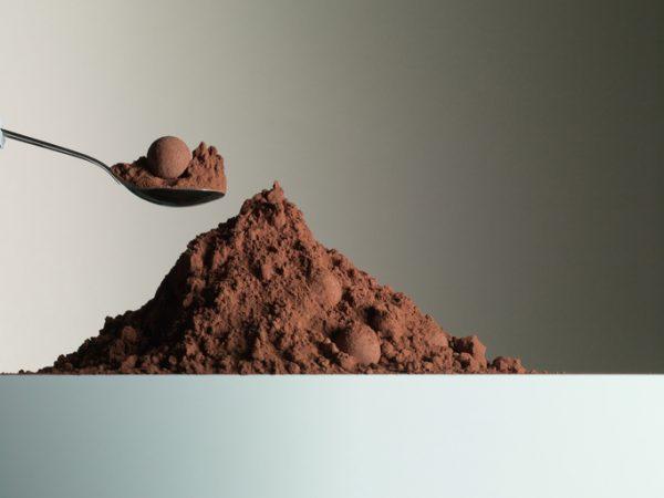 Spoon over heap of cocoa powder