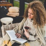 woman-reading-a-book-in-an-armchair-at-home-with-a-glass-of-wine