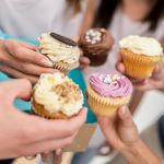 group-of-people-holding-cupcakes-in-a-circle
