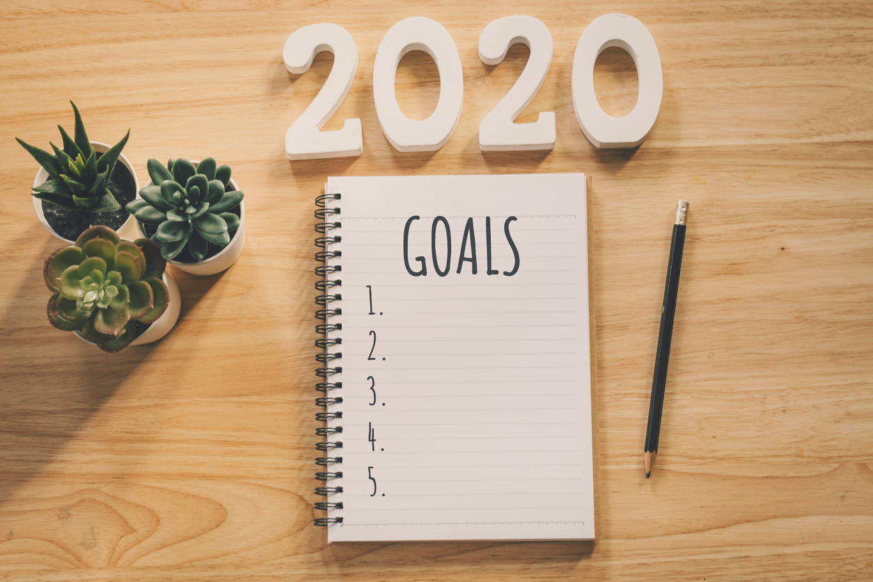 New year 2020 goals list. Office desk table with notebooks and pencil with pot plant.