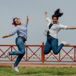 Two happy young women jumping in air