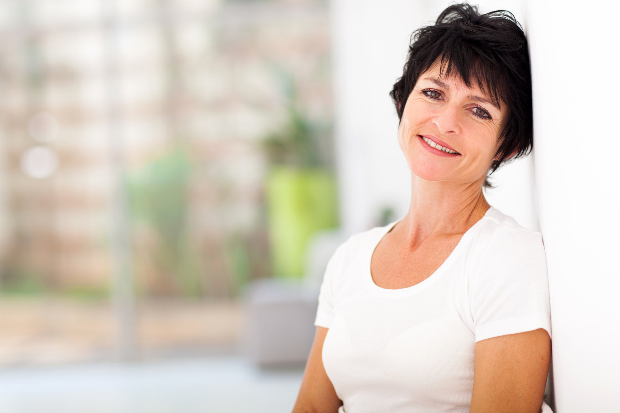 smiling woman with short brown hair wearing a white tshirt