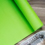 Lime green yoga mat next to water bottle