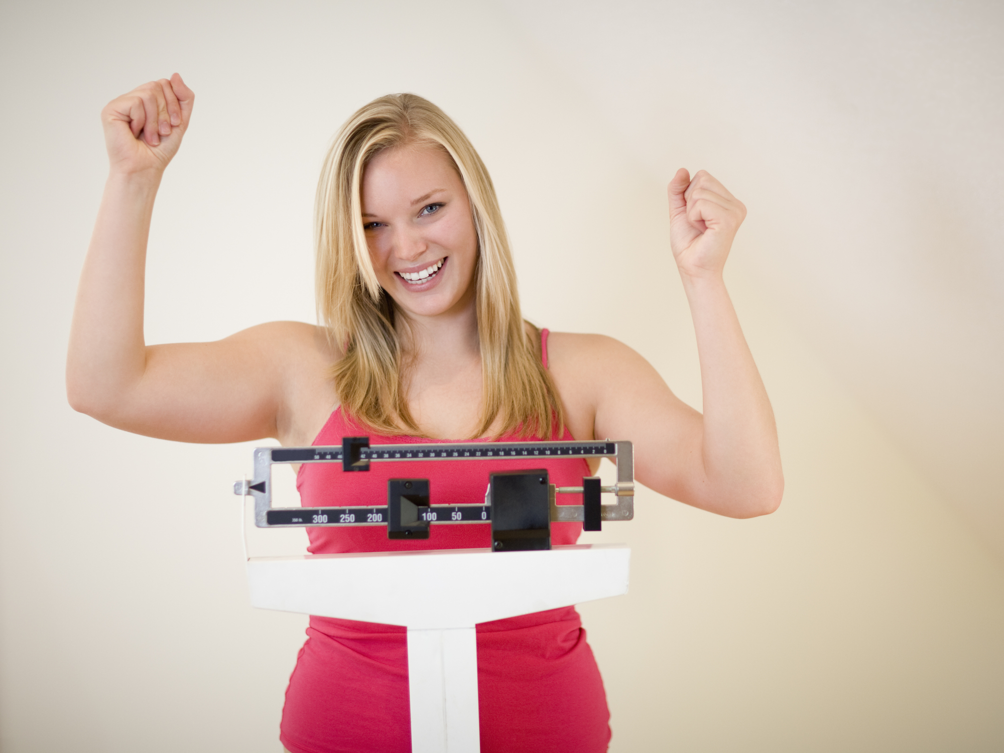 Happy blonde woman on weight scale