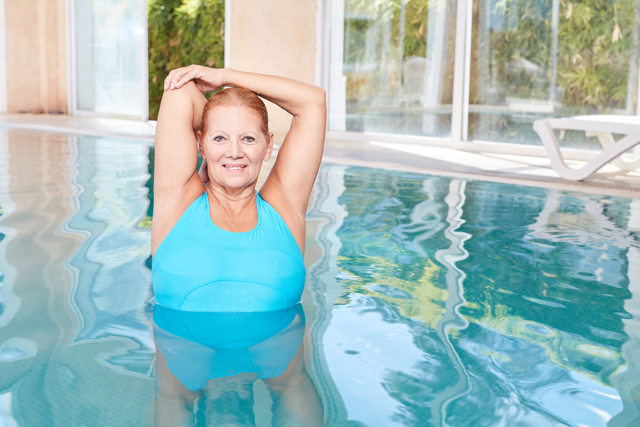 woman doing healthy stretching exercise during water aerobics